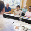 Mature students and their teacher in a classroom — Foto Stock
