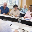 Mature students and their teacher in a classroom — Stock Photo