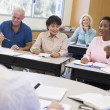 Stock Photo: Mature students and their teacher in a classroom