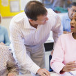 Teacher assisting mature student in class — Stock Photo