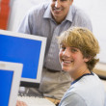 A teacher talks to a schoolboy using a computer in a high school — Stock Photo