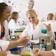School children and their teacher in a high school science class - Stock Photo