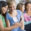 Teenage girls looking at a mobile phone - Stok fotoğraf