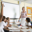 A teacher teaching a junior school class — Stock Photo