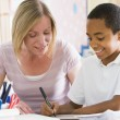 Stock Photo: A schoolboy sitting with his teacher in class