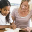 A schoolgirl and her teacher reading a book in class — Stock Photo