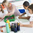 Schoolchildren and their teacher in an art class - Stock Photo