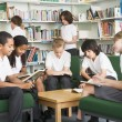 Junior school students working in a library — Stock Photo