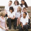 School children sitting on benches outside with their teacher — Stock Photo #4759637