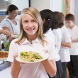 Schoolgirl holding plate of lunch in school cafeteria - Stock Photo