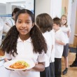 Schoolgirl holding plate of lunch in school cafeteria — Stock Photo #4759640