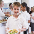 Schoolboy holding plate of lunch in school cafeteria — Stock Photo #4759648
