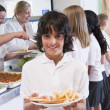 Schoolboy holding plate of lunch in school cafeteria — Stock Photo