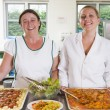 Lunchladies beside trays of food in school cafeteria - Stock Photo