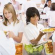 Lunchladies serving plates of lunch in school cafeteria — Stock Photo