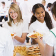 Lunchladies serving plates of lunch in school cafeteria — Stock Photo #4759667