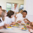 Schoolchildren enjoying their lunch in a school cafeteria — Foto Stock