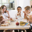 Schoolchildren enjoying their lunch in a school cafeteria — Stock Photo