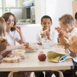 Schoolchildren enjoying their lunch in a school cafeteria - Stock Photo