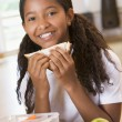 Schoolgirl enjoying her lunch in a school cafeteria — Stock Photo