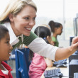 Royalty-Free Stock Photo: Teacher helping kindergarten children learn how to use computers
