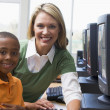 Stock Photo: Teacher helping kindergarten children learn how to use computers