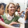 Teacher helping kindergarten children learn how to use computers — Stock Photo #4759709