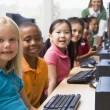 Kindergarten children learning how to use computers. - Stock Photo