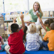 Kindergarten teacher reading to children in library — ストック写真