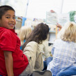 Kindergarten teacher reading to children in library, boy looking — Stock Photo