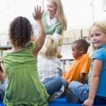 Kindergarten teacher reading to children in library, girl lookin — Stock Photo