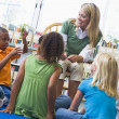 Kindergarten teacher and children looking at seedling in library — Stock Photo