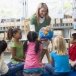 Kindergarten teacher and children looking at globe in library — Stock Photo