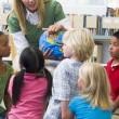 Kindergarten teacher and children looking at globe — Stock Photo