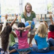 Kindergarten teacher and children with hands raised in library - Stock Photo