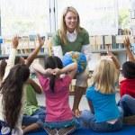 Kindergarten teacher and children with hands raised in library — Stock Photo