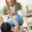 Kindergarten teacher and children looking at globe — Stock Photo #4759751