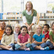 Kindergarten teacher sitting with children in library — Stock Photo #4759752