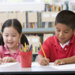 Kindergarten children sitting at desk and writing in classroom - Stock Photo