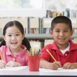 Kindergarten children sitting at desk and writing in classroom — 图库照片
