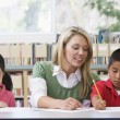 Kindergarten teacher helping students with writing skills — Stock Photo #4759758