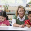 Kindergarten teacher helping students with writing skills — Stock fotografie #4759759
