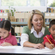 Kindergarten teacher helping students with writing skills — Foto Stock #4759759