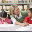 Kindergarten teacher helping students with writing skills — Stock Photo #4759761