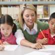 Kindergarten teacher helping students with writing skills — Stock Photo #4759762