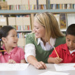 Kindergarten teacher helping students with writing skills — Stok fotoğraf