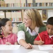 Kindergarten teacher helping students with writing skills - Stock Photo