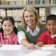 Kindergarten teacher helping students learn writing skills — Stock Photo