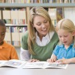Kindergarten teacher helping students with reading skills — Stock Photo #4759766