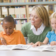 Kindergarten teacher helping students with reading skills — Stock Photo